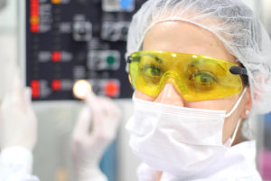 a female technician is monitoring the process of pill packaging.